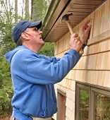 Carpenter nailing cedar shingles to exterior wall
