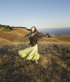 Passionate woman dancing on hillside