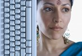 Indian woman wearing bindi next to computer keyboard