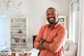 Portrait of smiling mature man with beard standing with crossed arms. Confident african man with fol poster