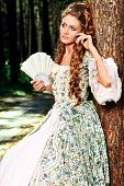 Beautiful young woman in medieval era dress on a sunny day outdoor.