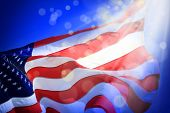 Conceptual image of waving American flag and light beam with abstract lights over blue background poster