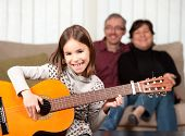 little girl playing guitar with her family at home