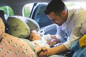 Divorced Father Taking His Baby From A Baby Seat. poster