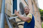 stock photo of air conditioner  - Young setup man installs the new air conditioner for office - JPG