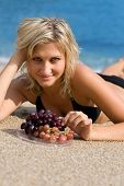 Beautiful girl with grapes on the beach by the sea.