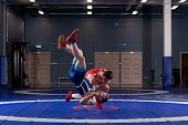 Two Young Men In Blue And Red Wrestling Tights Are Wrestlng And Making A Hip Throw On A Yellow Wrest poster