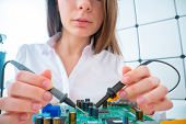 Young woman with measuring devices in the electronics engineer  laboratory poster