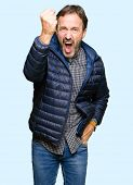 Middle age handsome man wearing winter coat angry and mad raising fist frustrated and furious while  poster