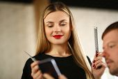Woman Hairdresser Looking At Client Mobile Phone. Young Hairstylist Holding Comb And Scissors In Han poster