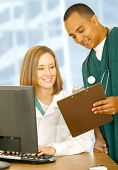 pic of medical staff  - two medical people looking at same clip board and smiling - JPG