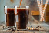 Ice Coffee In A Tall Glass With Cream Poured Over, Coffee Ice Cubes And Beans On A Old Rustic Wooden poster