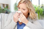 cold, allergy and health problem concept - ill woman or allergic blowing nose to tissue at home poster