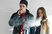 Vape Teenager. Young Cute Girl In Casual Clothes And Handsome Guy In A Cap Smoke An Electronic Cigar poster