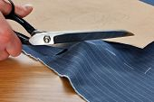 Photo of a piece of pinstripe material being cut around a bespoke template