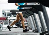 stock photo of cardio exercise  - woman running on a treadmill in a fitness club - JPG