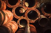 stock photo of scrap-iron  - Rusty old pipes stacked up with natural light on them - JPG