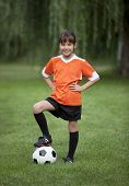 Full length photo of young girl standing with foot on soccer ball.