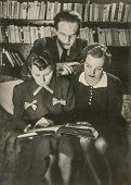 POZNAN, POLAND, CIRCA 1937 - Vintage photo of two young women and a man browsing a photo album, Poznan, Poland,circa 1937