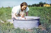 stock photo of washtub  - Vintage photo of mother bathing her baby daughter in a washtub  - JPG