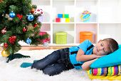 Little boy sleeping under Christmas Tree waiting for Santa Claus to come