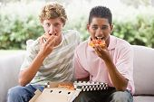 Teenage Boys Sitting On Couch Eating Pizza Together