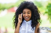 Outdoor Portrait Of A Teenage Black Girl Using A Mobile Phone - African People