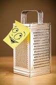 Drawn smiley face on a post-it note sticked on grater