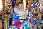 image of merry-go-round  - happy smiling son and his handsome father spending fun time together at amusement park riding merry - JPG