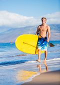 Man with Stand Up Paddle Board, SUP, on the beach in Hawaii
