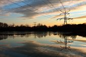 image of electricity pylon  - Electricity pylon with reflection in water at sunset - JPG