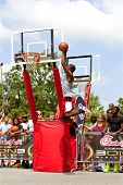 Young Man Jumps High In Outdoor Basketball Slam Dunk Contest