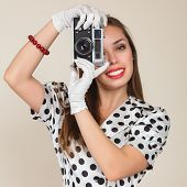 pic of dress-making  - Young woman in retro style dress and white gloves making photos with vintage film camera against studio background - JPG