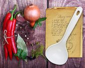 foto of cayenne pepper  - Spices and old recipe book on wooden background - JPG