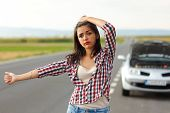 Woman Hitch-hiking In Front Of Her Broken Car