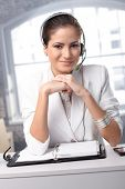 Confident customer service operator at office desk wearing headset, smiling at camera.