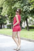 Young woman in red shorts and a blouse on the summer park