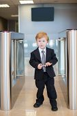 A little boy in a suit at the entrance to the business center with card in hands