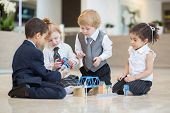 Children in business dress playing with toys in the business center