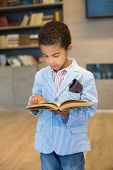 Little mulatto boy in a modern striped jacket read a book in library