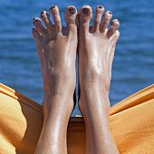 stock photo of human toe  - sandy crazy woman toes moving and relaxing on the beach - JPG