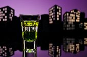 Absinthe shot in nice colorful cityscape setting