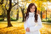 Beautiful young woman smiling  in the autumn fall