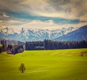 Vintage retro hipster style travel image of German idyllic pastoral countryside in spring with Alps in background. Bavaria, Germany