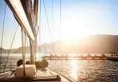Sailboat on sunset, luxurious water transport, bright sun light on the sea, evening travel on sail y