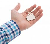 Close-up Of Hand Giving A Key Ring With House Isolated On White Bacground