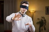 Blindfolded Young Man At Home In Living Room Cannot See