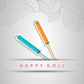 Indian festival Happy Holi celebrations concept with colour gun on floral decorated background.