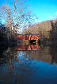 pic of covered bridge  - The Foxcatcher red Covered Bridge reflecting in the blue waters below - JPG