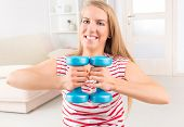 Young woman doing exercise with dumb bell, strengthen her arms and shoulders at home